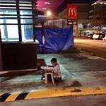 Megindító fotó – egy gyorsétteremből kiszűrődő fénynél tanul egy hajléktalan kisfiú