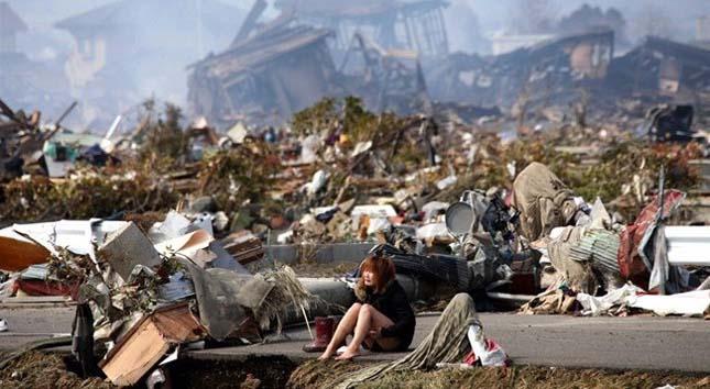 Egy lány ül a roncsok között a japán cunami után